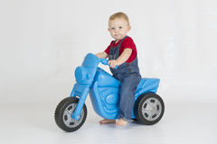 Baby boy riding his plastic scooter Royalty Free Stock Photography