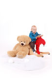 Baby Boy is riding a rocker. Blond Infant rides a red rocking horse. he is very cute. he is smiling into the cam. he is very happy because his lucky teddy bear Stock Image