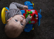 Baby boy riding in toy aeroplane on carpet. Royalty Free Stock Photo