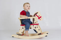 Baby boy riding a wooden rocking horse Stock Photo
