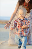Baby boy running from mother Stock Images