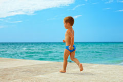 Baby boy running on the pier near the blue sea Stock Photography