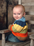 Baby Boy on Rustic Chair. Baby boy in chair looking over shoulder Stock Photo