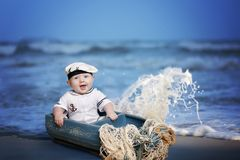 Baby boy sailor. Portrait of laughing baby boy in sailor costume sitting in a gray colored boat on the beach with breaking waves behind and ropes lying over the stock photos