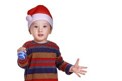 Baby boy with a Santa cap looking amazed and halding a bauble. Baby boy with a Santa cap looking amazed and holding a blue Christmas decoration Royalty Free Stock Image