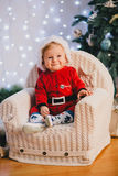 Baby-boy in Santa Claus suit sitting under the Christmas tree Stock Image