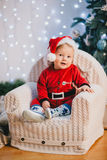 Baby-boy in Santa Claus suit sitting under the Christmas tree Royalty Free Stock Photo