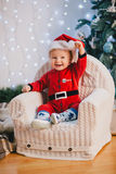 Baby-boy in Santa Claus suit sitting under the Christmas tree Stock Photos