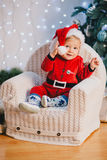 Baby-boy in Santa Claus suit sitting under the Christmas tree Royalty Free Stock Image