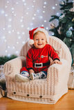 Baby-boy in Santa Claus suit sitting under the Christmas tree Stock Photography