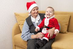 Baby boy in Santa costume with his grandmother. Baby boy in Santa costume with his great grandmother Royalty Free Stock Photo