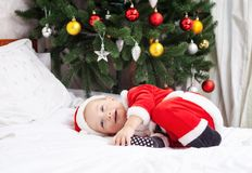 Baby boy in Santa costume lying on bed Royalty Free Stock Photos
