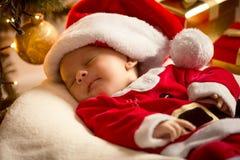 Baby boy in Santa costume lying under Christmas tree. Christmas Stock Photos