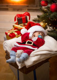 Baby boy in Santa costume sleeping on Christmas night at living Stock Photos