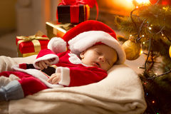 Baby boy in Santa costume sleeping at fireplace next to Christma Royalty Free Stock Images
