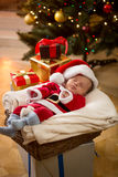Baby boy in Santa costume sleeping under Christmas tree Royalty Free Stock Photo