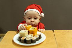 Baby boy in santa hat takes sishi from the plate royalty free stock photography