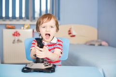 Baby boy screaming when playing computer games. With joystick Royalty Free Stock Image