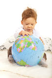 Baby boy searching on world globe Stock Photo