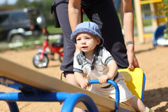 Baby boy on seesaw Stock Photos