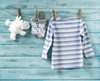 Baby boy shirt, socks and white toy bear on a clothesline Royalty Free Stock Image