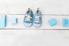 Baby boy shoes and wooden toys on wooden background. Flat lay royalty free stock photography