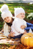 Baby boy with sister in autumn park Stock Photo