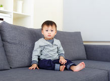 Baby boy sit on sofa. At home Stock Images