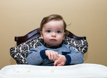Baby Boy Sits in High Chair, Plays With Hands. Baby boy in high chair plays with his hands Stock Photo