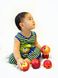 Baby boy sits with red apples Royalty Free Stock Image