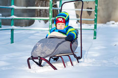 Baby boy sits on sled. Little Baby boy sits on sled sunny snowy winter weather Royalty Free Stock Images
