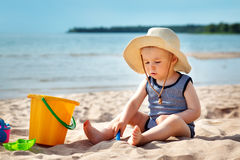 Baby boy sitting on the beach in summer day Stock Photos
