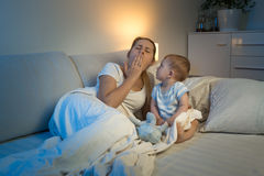 Baby boy sitting on bed and looking at yawning tired mother Stock Image