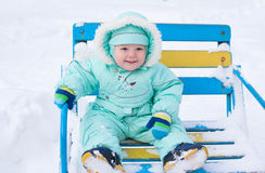 Baby boy sitting on bench in park in winter. Turquoise clothing coveralls and smiling Stock Photos