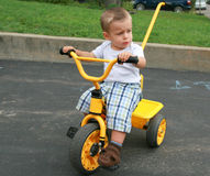 Baby boy sitting on a bicycle. Baby boy learning to ride a tricycle Stock Photo