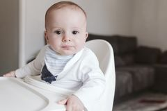 Baby boy sitting on chair ready to eat baby food. Home, indoor.  stock photography