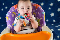 Baby boy is sitting at the childrens table. With asterisks and playing with a rattle stock images