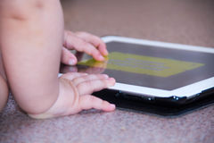 Baby boy is sitting on floor playing with tablet pc. Close-up photo of the hands. Little touch pad, early learning. Royalty Free Stock Photos