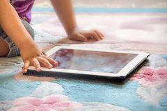 Baby boy sitting on floor playing with tablet pc. Close-up photo of the hands. Little touch pad, early learning. Royalty Free Stock Photo
