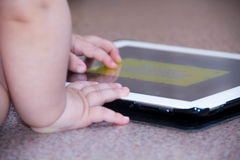 Baby boy is sitting on floor playing with tablet pc. Close-up photo of the hands. Little touch pad, early learning. royalty free stock images