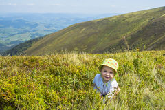 Little baby playing with grass in the mountains in summer. Baby boy sitting in the grass. Beautiful mountains landscape Royalty Free Stock Photo
