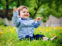 Baby boy sitting on the grass in field. Happiness Baby boy sitting on the grass in field Royalty Free Stock Photography