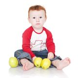Baby boy sitting with green apples Stock Images