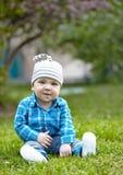 Baby boy sitting on green grass Royalty Free Stock Photos