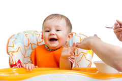 Baby boy sitting in high chair and eating with a spoon Stock Images