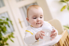 Baby boy sitting in high chair and holding a bottle Stock Photography