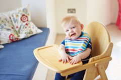 Baby Boy Sitting In High Chair Stock Image
