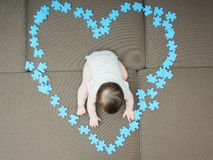 Baby boy sitting in the middle puzzle pieces folded as shape of heart on sofa at home living room Stock Image