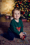 Baby boy sitting near Christmas tree Royalty Free Stock Images
