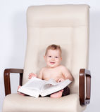 Baby boy sitting in office chair reading book Stock Images